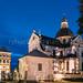 Nesvizh, Minsk Region, Belarus. Corpus Christi Church And Castle Tower In Evening Or Night Illuminations. Famous Landmarks In Nyasvizh
