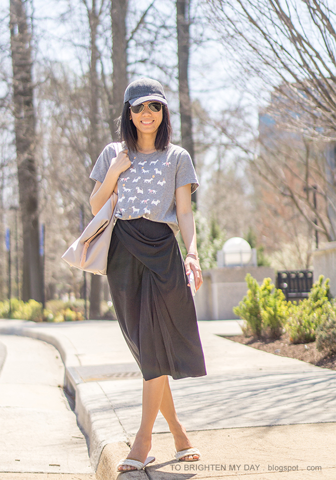 gray wool baseball cap, dog patterned graphic tee, dark gray draped skirt, beige and gray tote, white embellished slides