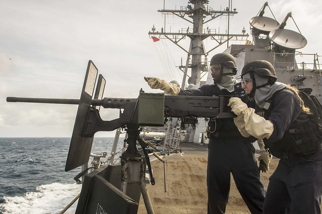 GULF OF THAILAND (June 18, 2018) Fire Controlmen 2nd Class Treveion Thorn, left, and Katherine Swol fire a .50 caliber machine gun from the guided-missile destroyer USS Mustin (DDG 89) during a live-fire gunnery exercise with Royal Thai Navy vessels as part of Cooperation Afloat Readiness and Training (CARAT) Thailand 2018. The CARAT exercise series, in its 24th iteration, highlights the skill and will of regional partners to cooperatively work together towards the common goal of ensuring a secure and stable maritime environment. (U.S. Navy photo by Mass Communication Specialist 3rd Class Christopher A. Veloicaza)