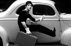 Mime running beside classic hot Rod Car