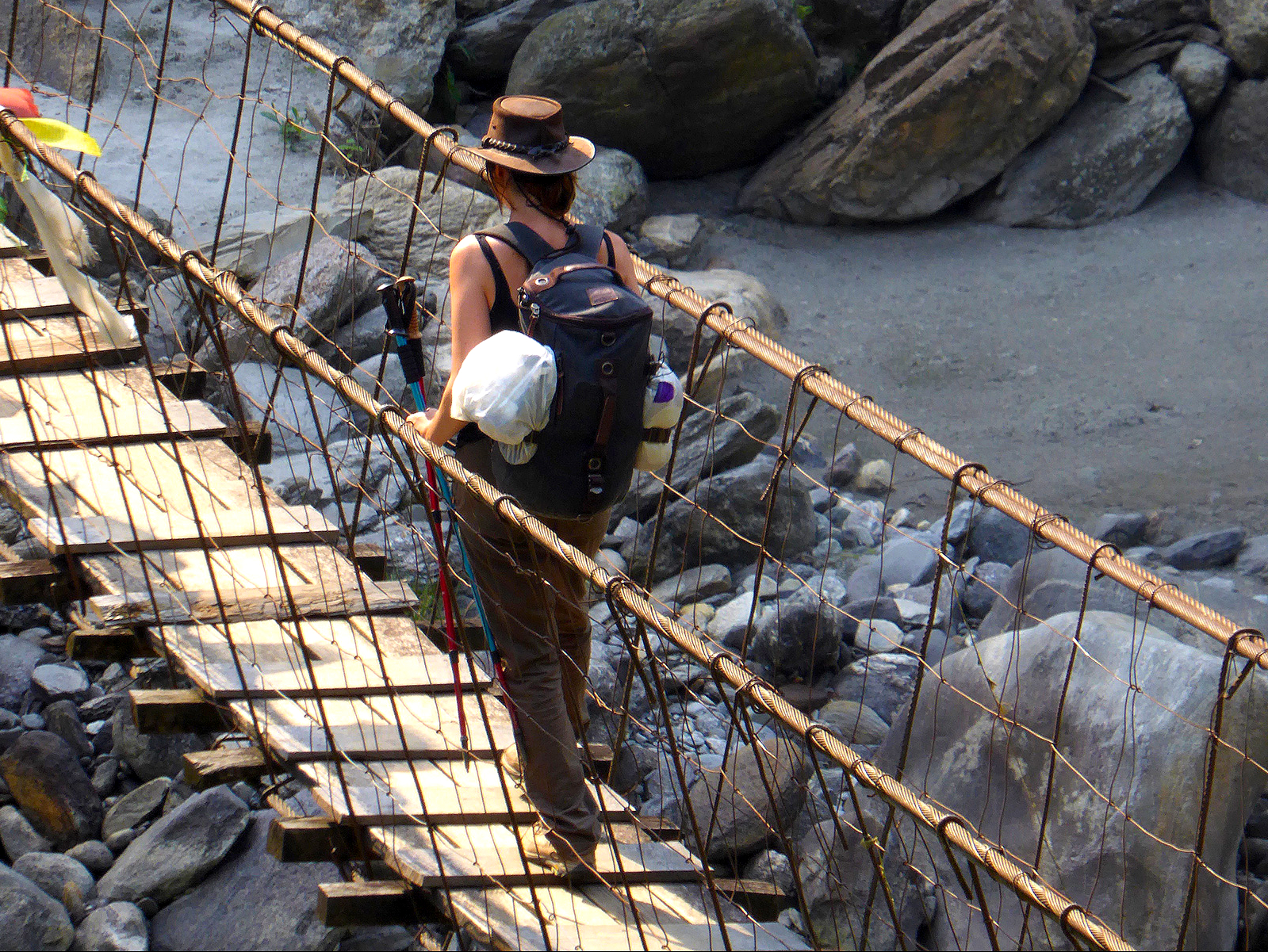 female trekker crossing one of the many swing bridges that occur along the criss -cross Annapurna Base Camp, and Annapurna Poon hill treks in Nepal