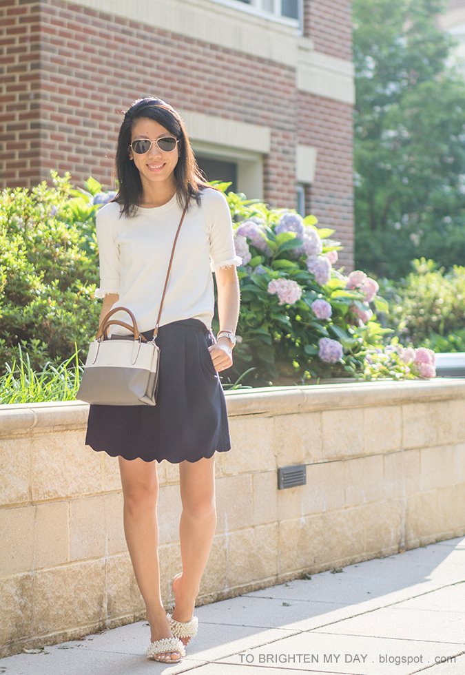 white sweater tee with fringe, colorblocked crossbody bag, navy scalloped skirt, pearl encrusted heels, two tone watch