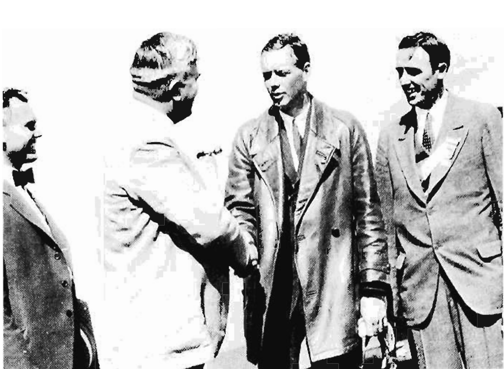 Upon landing at Little Falls, Lindbergh shook hands with Minnesota Governor Theodore Christianson while Mayor Grimes (right) looked on.