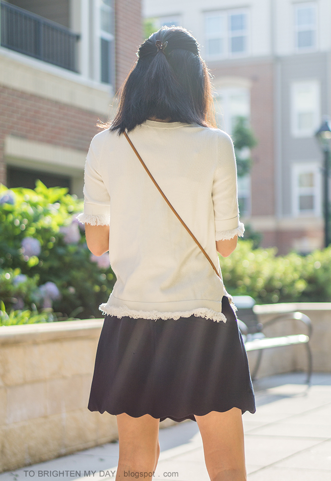 white sweater tee with fringe, colorblocked crossbody bag, navy scalloped skirt