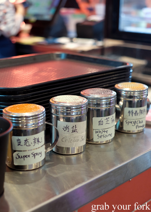 Self-serve seasonings at the counter at Granny Wolf BBQ in Central Park Mall Sydney