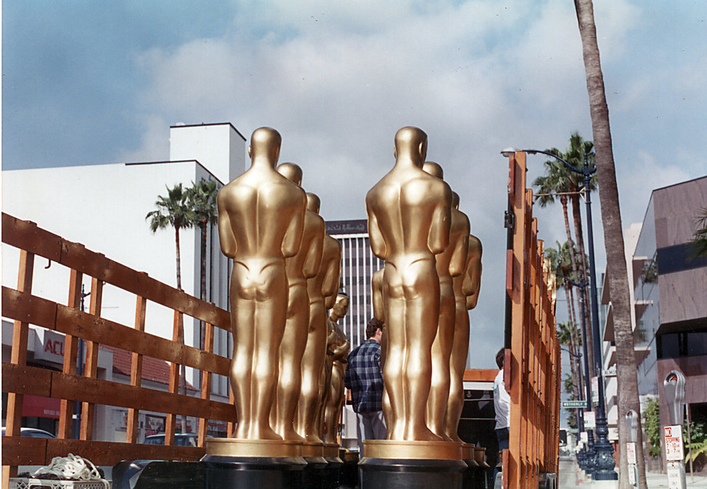 a truck full of giant oscar statues with their backs turned