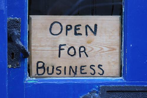 "Wooden sign in door that says ""Open For Business."""