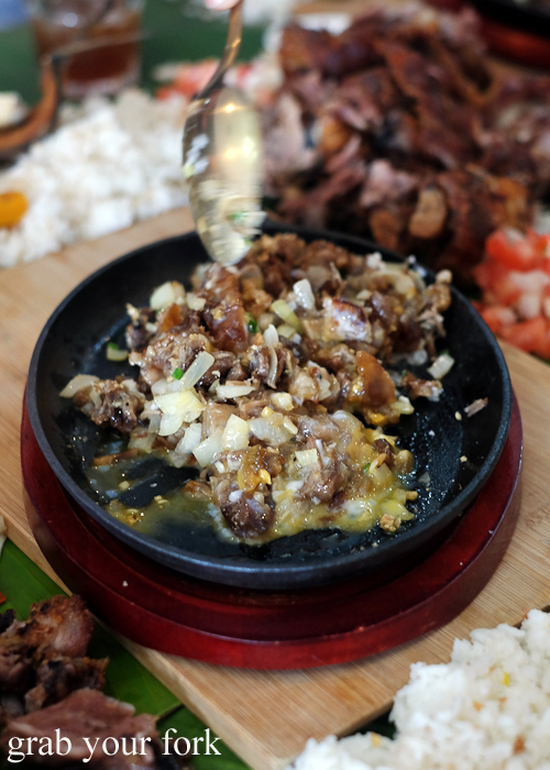 Stirring the egg yolk into sizzling sisig for our boodle fight at Sizzling Fillo in Lidcombe Sydney