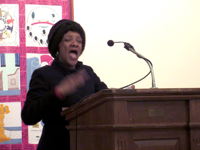 A woman in a black coat and matching winter hat speaks passionately at a podium.