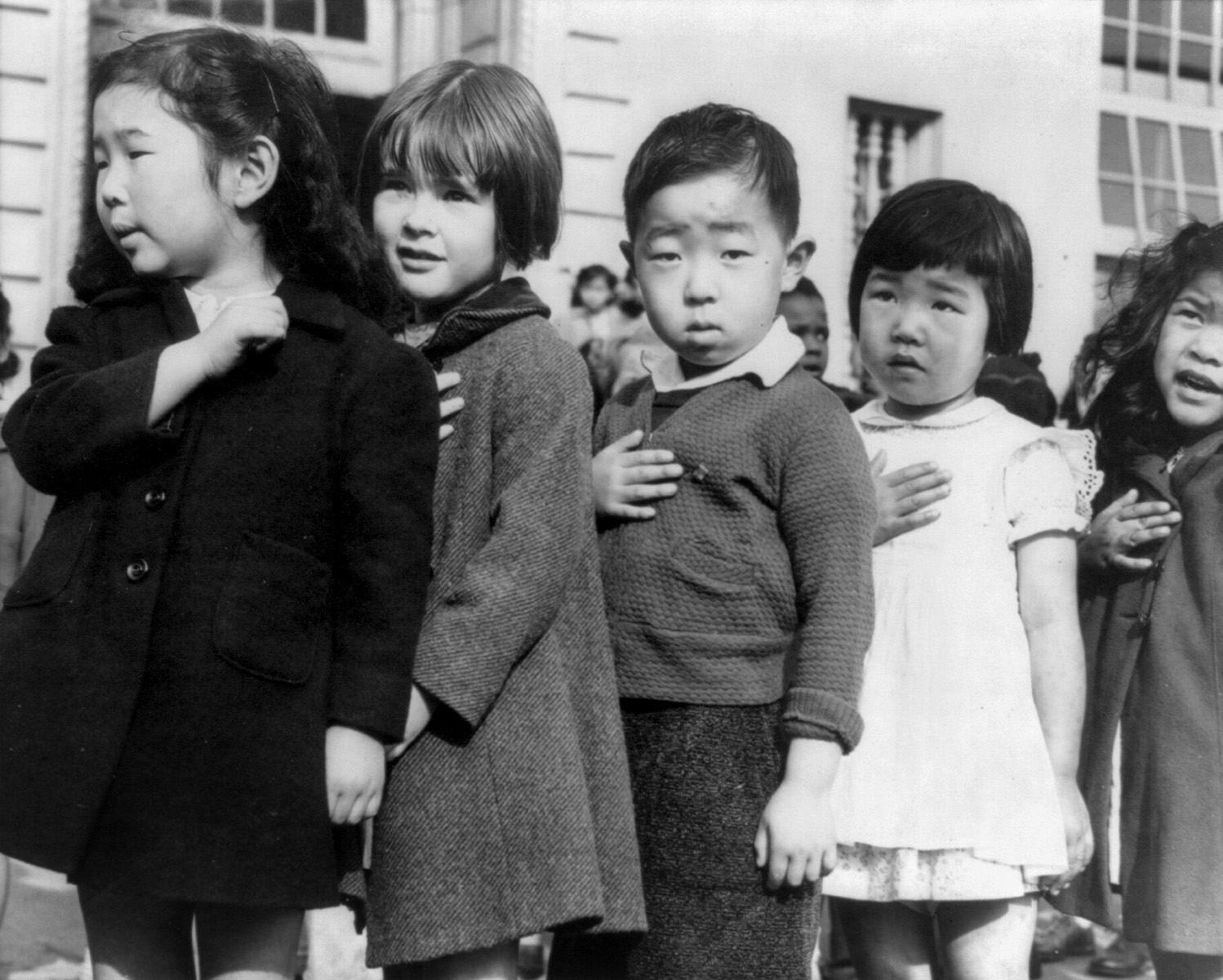 First-graders, some of Japanese ancestry, at the Weill public school, San Francisco, Calif., pledging allegiance to the United States flag. (1942, photo by Dorothea Lange).