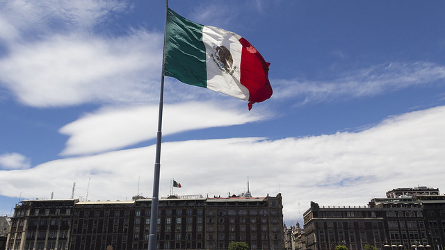 Mexico flagpole with buildings in the background
