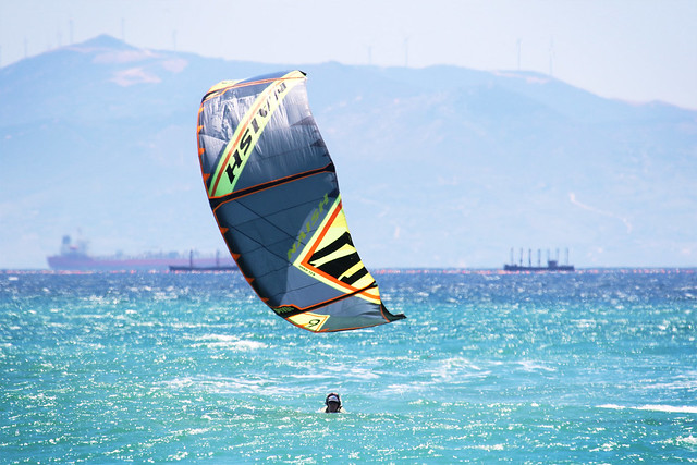A kite above the water with a head below. Kitesurfing in Tarifa, Spain.