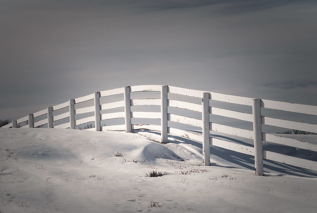 Wood Fence over Snow Covered Hill