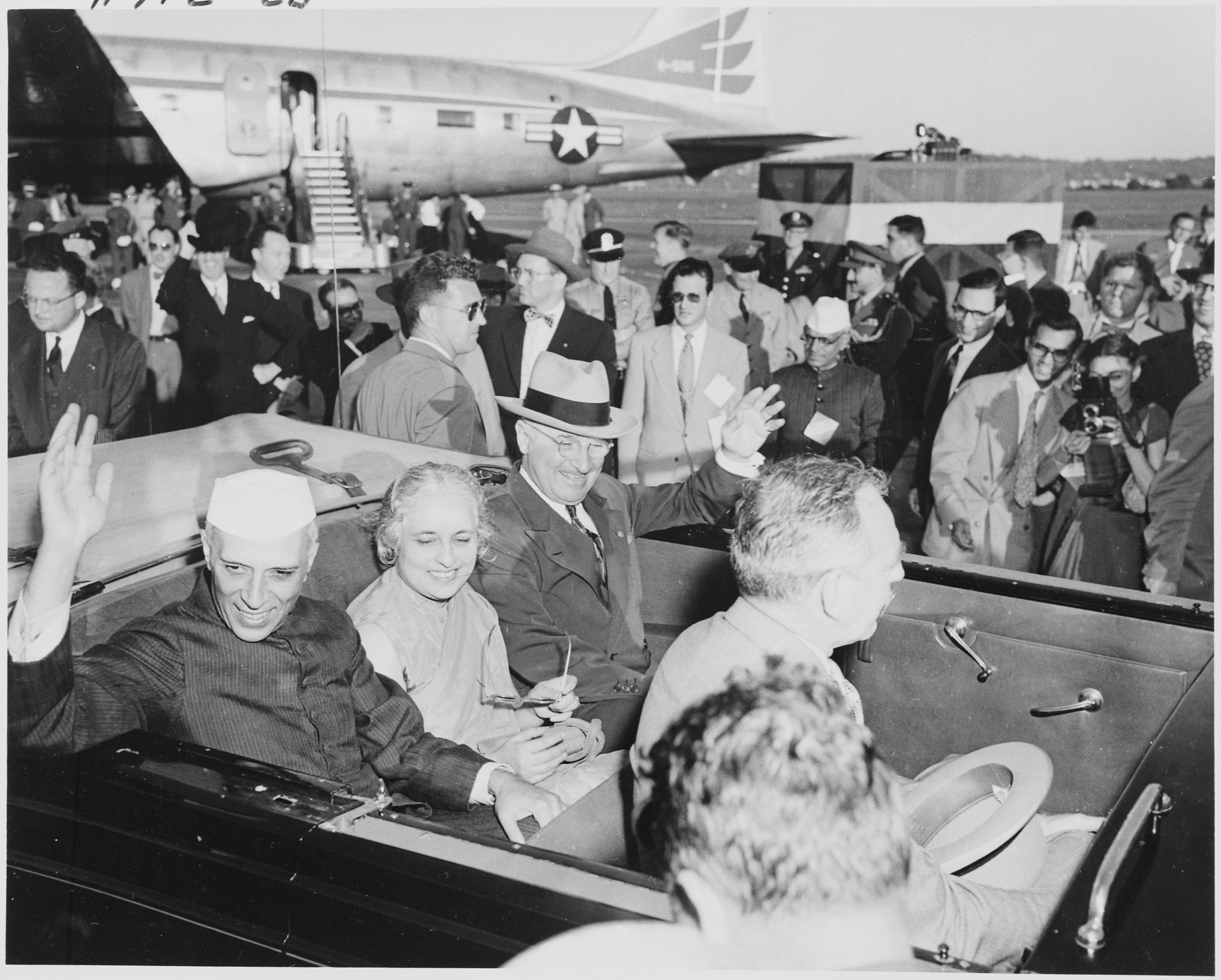 U.S. President Harry S. Truman and Indian Prime Minister Jawaharlal Nehru, with Nehru's sister, Madame Pandit, waving from their limousine as they leave Washington National Airport, during Nehru's visit to the United States. Photo taken by Abbie Rowe on October 11, 1949. From the holdings of the National Archives and Records Administration. Office of Presidential Libraries. Harry S. Truman Library. (04/01/1985 - ), cataloged under the National Archives Identifier (NAID) 200154.