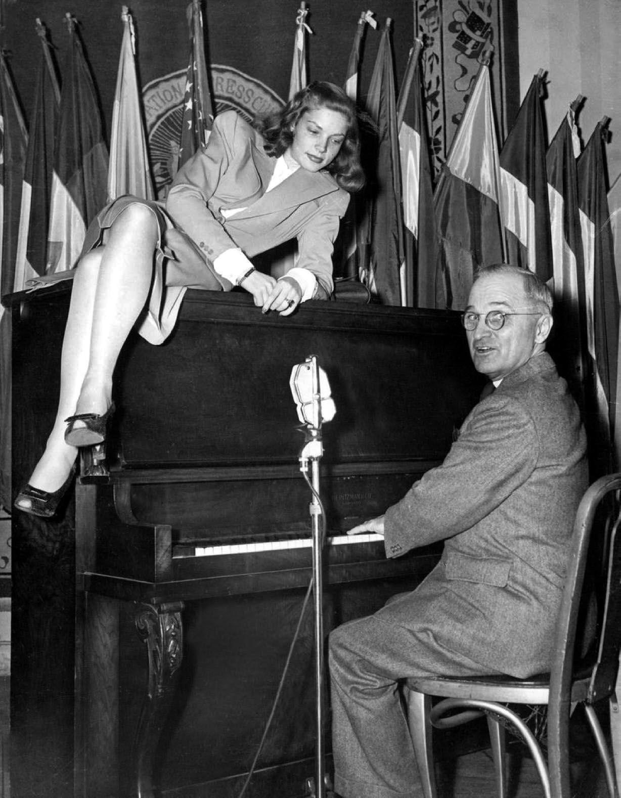 Actress Lauren Bacall lounges on top of the piano while Vice President Truman plays an old-fashioned waltz for servicemen at the National Press Club Canteen in Washington, D.C. on February 10, 1945. The photograph was published in the February 26, 1945, issue of LIFE magazine where the text reads: