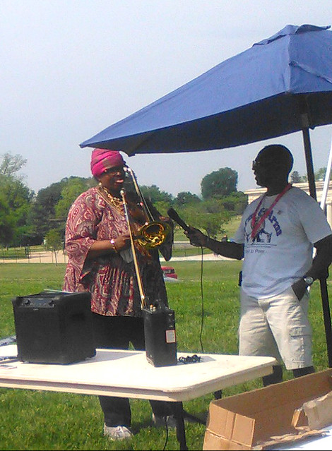 Photo of a woman playing a trombone, outdoors under a canopy, while a man holds a microphone.