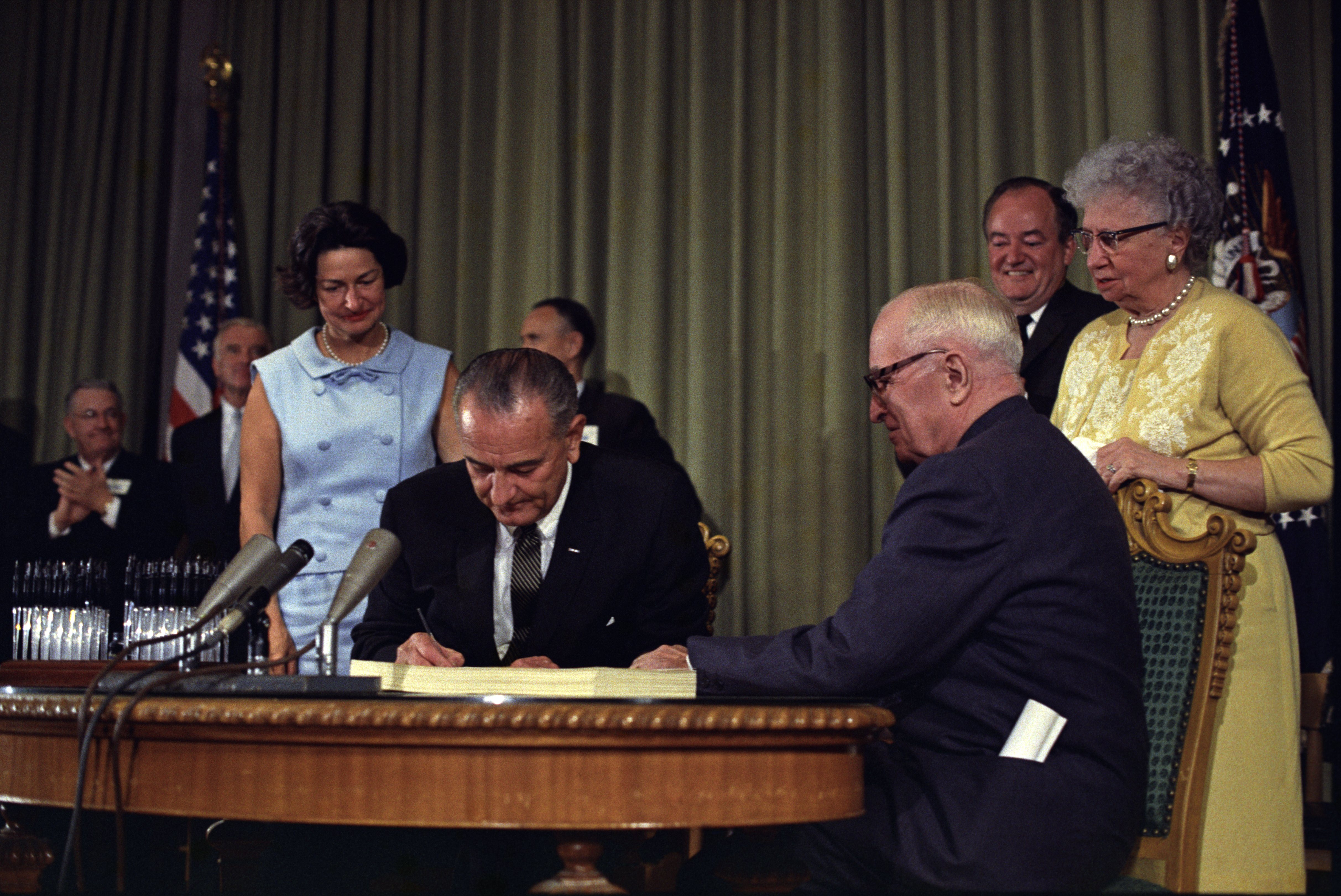 U.S. President Lyndon B. Johnson signing the Medicare Bill at the Harry S. Truman Library in Independence, Missouri, on July 30, 1965. Former president Harry S. Truman is seated at the table with President Johnson. The following are in the background (from left to right): Senator Edward V. Long, an unidentified man, Lady Bird Johnson, Senator Mike Mansfield, Vice President Hubert Humphrey, and Bess Truman. Photo from the holdings of the National Archives and Records Administration, cataloged under the National Archives Identifier (NAID) 596403.