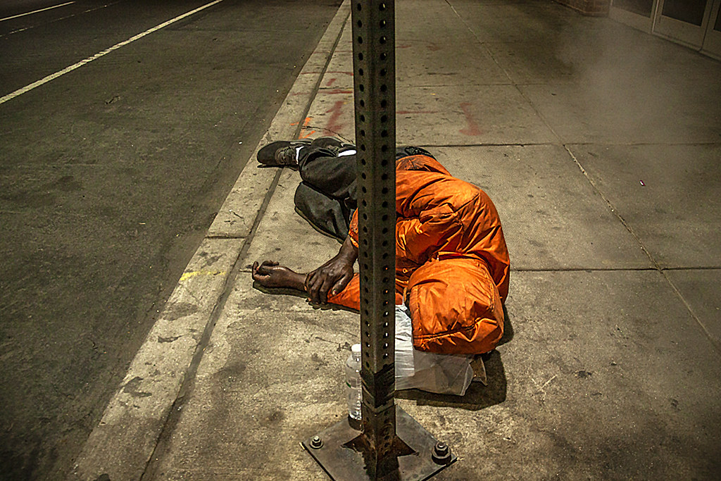 Man in orange jacket lying on sidewalk--outside Convention Center