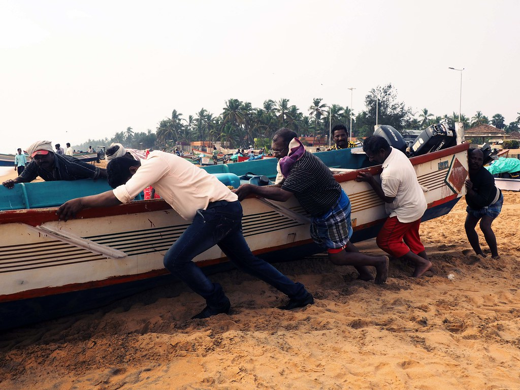Pushing fishermen boat Kerela Trivandrum beach _effected