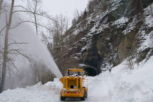 Going-to-the-Sun Road, park road crew clearing snow from road below West Tunnel in Glacier National Park, Montana. Photo taken by U.S. Dept. of Transportation, Federal Highway Administration, Office of Federal Lands Highway.