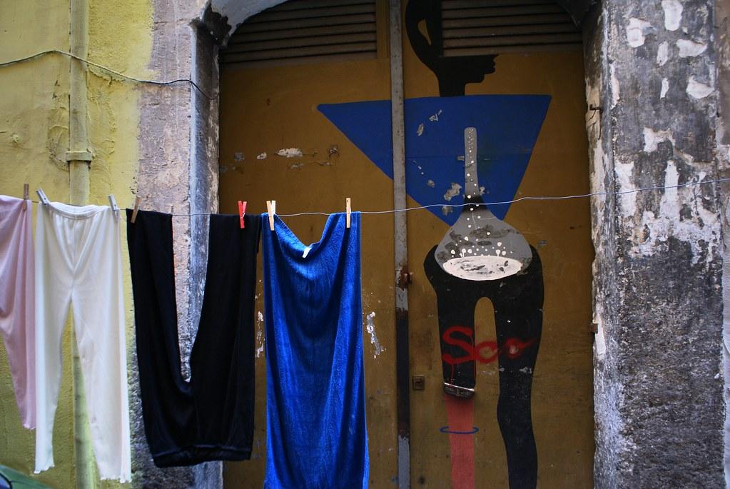 Le linge sèchent devant une fiole mystérieuse sur un mur des Quartiers Espagnols à Naples