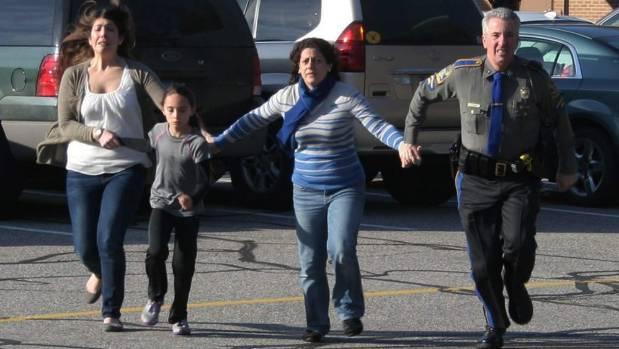 Túlélőket menekít biztonságos helyre egy rendőr a Sandy Hook-mészárlás alatt (fotó: AP)