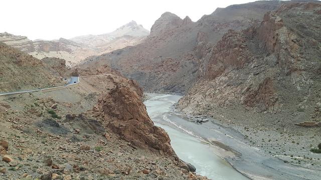 Rocky Mountain road with a river through valley on drive to Sahara desert tour, Morocco