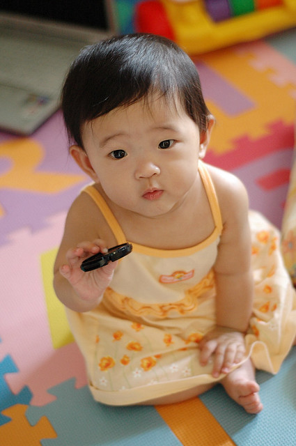Renice, holding the lens cap of my Nikkor 50mm f/1.8 lens, at 8 months, 29 days