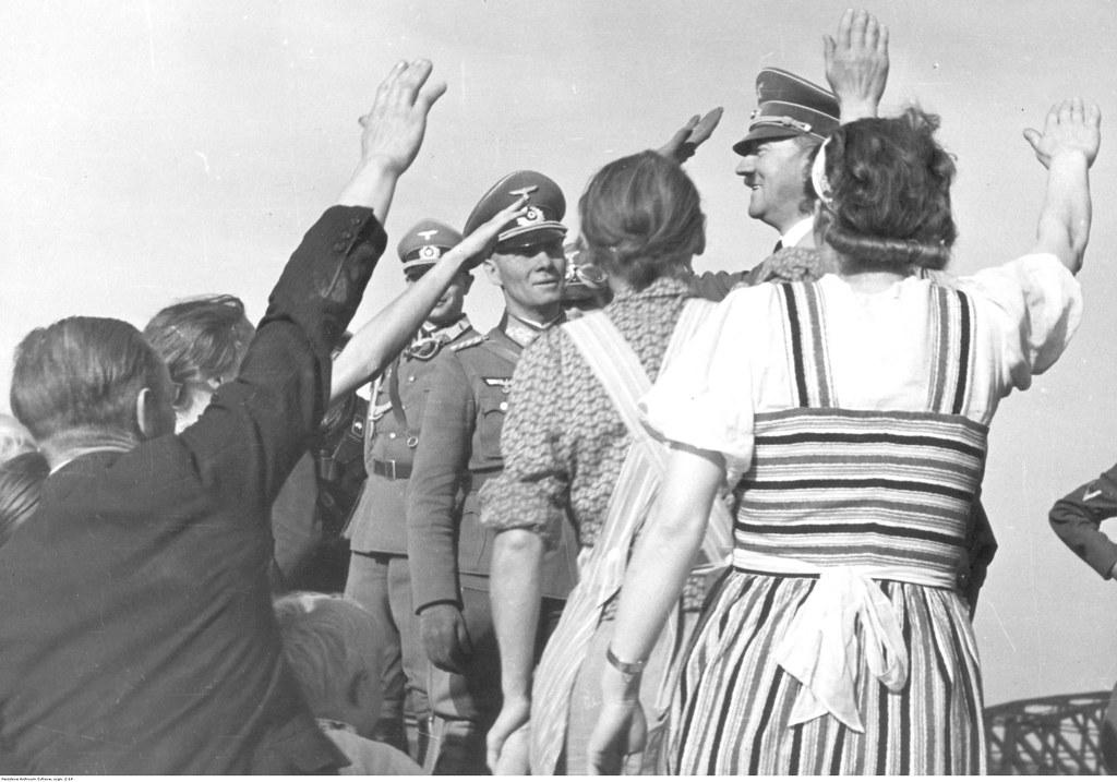 Фольксдойче встречают Адольфа Гитлера нацистским приветствием. Рядом с Гитлером виден генерал Эрвин Роммель