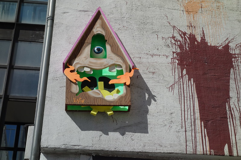 Street Art: A 3D house installed on a house facade, it has a mouth with teeth and an eyeball and a sun on its tongue.