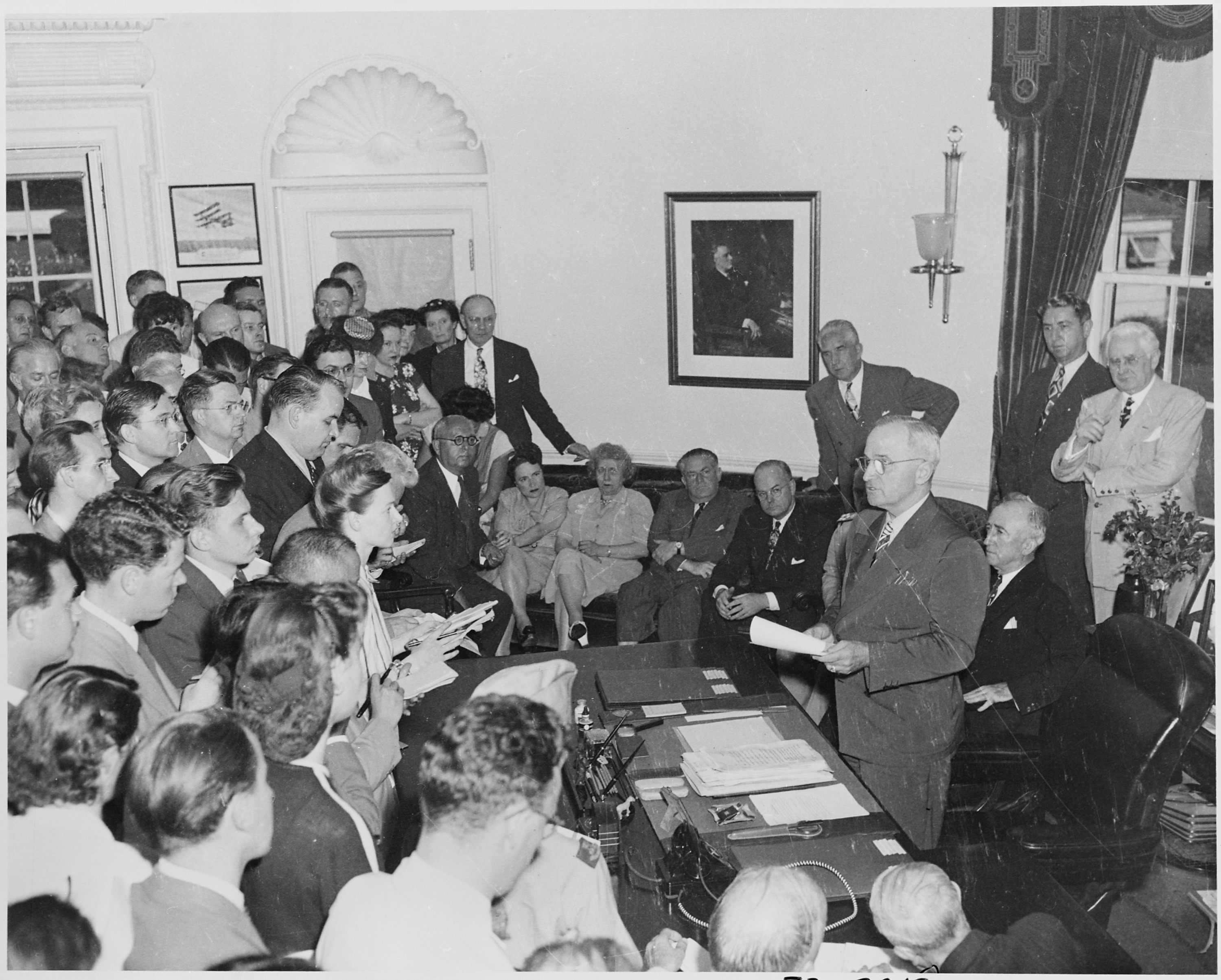 President Harry S. Truman in the Oval Office, reading the announcement of Japan's surrender to assembled reporters and officials on August 14. 1945. Photo from the National Archives and Records Administration. Office of Presidential Libraries. Harry S. Truman Library. (04/01/1985 - ), cataloged under the National Archives Identifier (NAID) 199171.