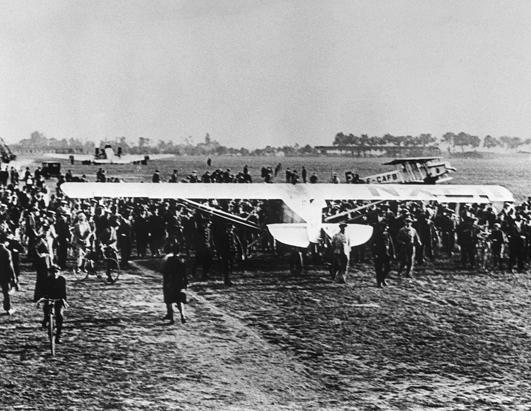 The Spirit of St. Louis on the runway at Le Bourget Aerodrome in Paris, France, surrounded by a far smaller crowd than the estimated 150,000 that greeted his arrival during the night of May 21, 1927. Patches can be seen along the fuselage, repairing damage done by the large crowd shortly after his landing. The photograph was likely taken on May 28, 1927.