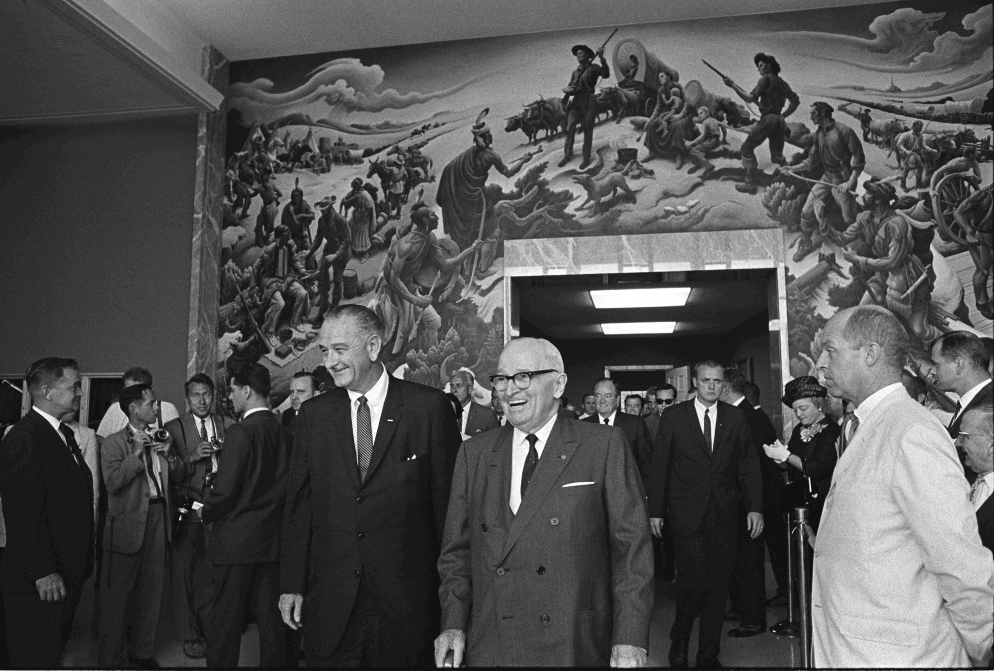 U.S. President Lyndon Johnson, former president Harry S. Truman, and others walk through the Harry S. Truman Library and Museum during the Medicare Bill signing event. LBJ Library photo by Yoichi Okamoto, A986-26a. Taken July 30, 1965.