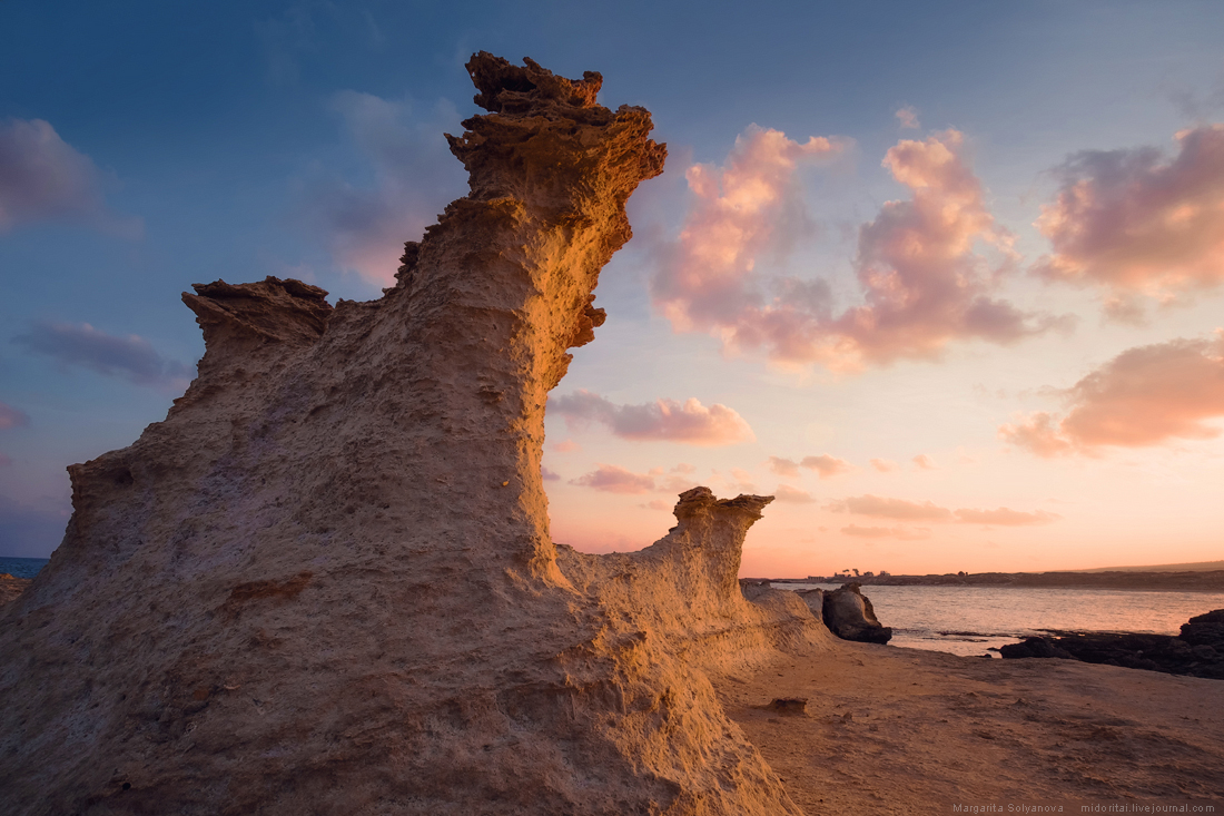 Sandrock figure in the light of sunrise on a rocky beach Northern Cyprus