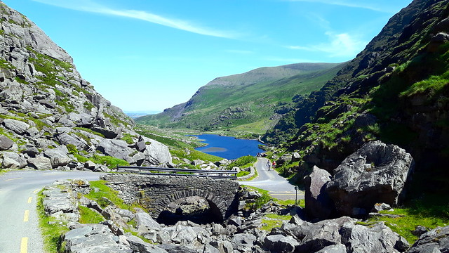 Winding road through Gap of Dunloe, Killarney Ireland with mountains and blue lake.