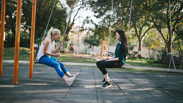 Two women sitting in park swings talking and smiling