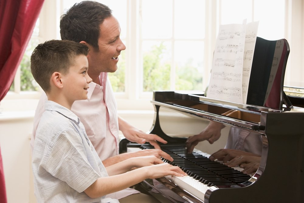 teacher and young student at the piano