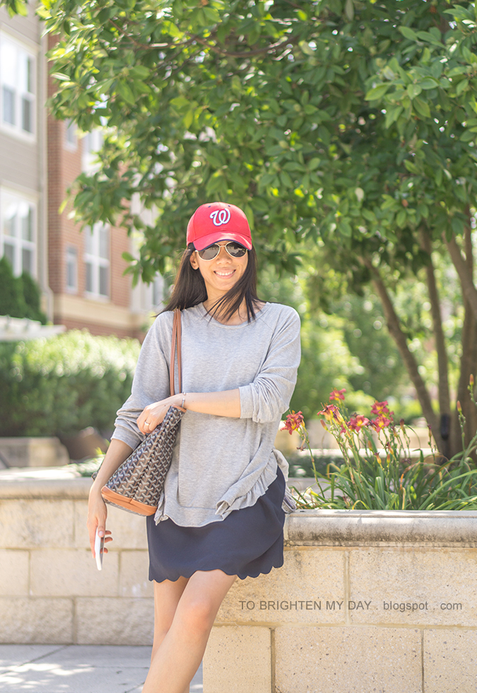 red baseball cap, gray tunic with side ruffle, silver cuff, patterned tote, navy scallop skirt