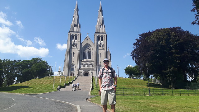 A man in front of a large cathedral.