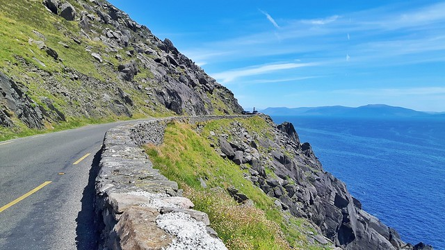 A narrow road on a mountain edge with the blue Atlantic Ocean below, Ireland.