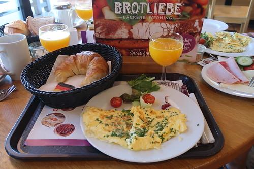 Rührei mit Croissant und frisch gepresstem Orangensaft