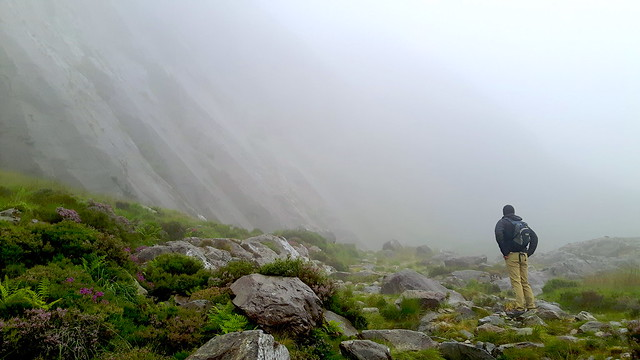 A man standing in front of a cliff in the clouds at Llyn Ogwen, Wales