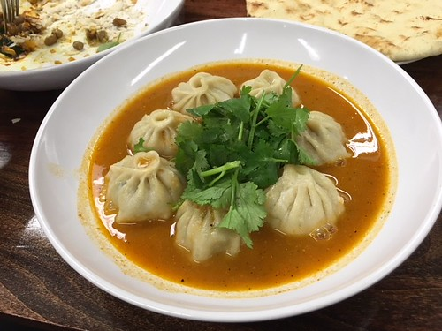 Momos bathed in sauce. From Momos: 5 Things You Need to Know About this Nepalese Favorite