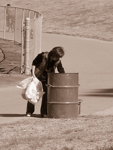 Homeless Woman searching for cans and bottles