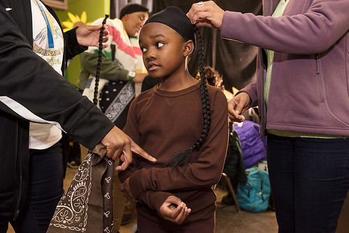 Wild Opelousas Princess Amiya gets help with her braids while  the tribe prepares to show their suits their classmates and teachers on Febuary 8, 2017. Photo by rhrphoto.com.