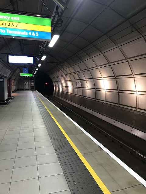 An empty train platform with a small red light in the entrance of the dark tunnel.