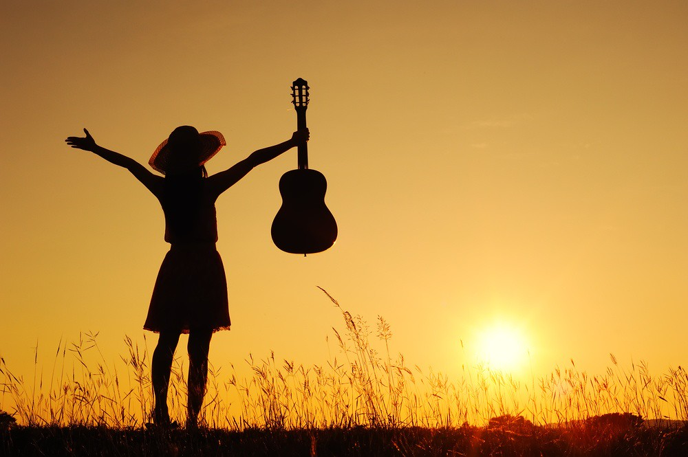 woman raising arms and guitar at sunset