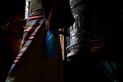 Tibetan woman walking near a large prayer wheel at Boudhanath Stupa, Kathmandu, Nepal