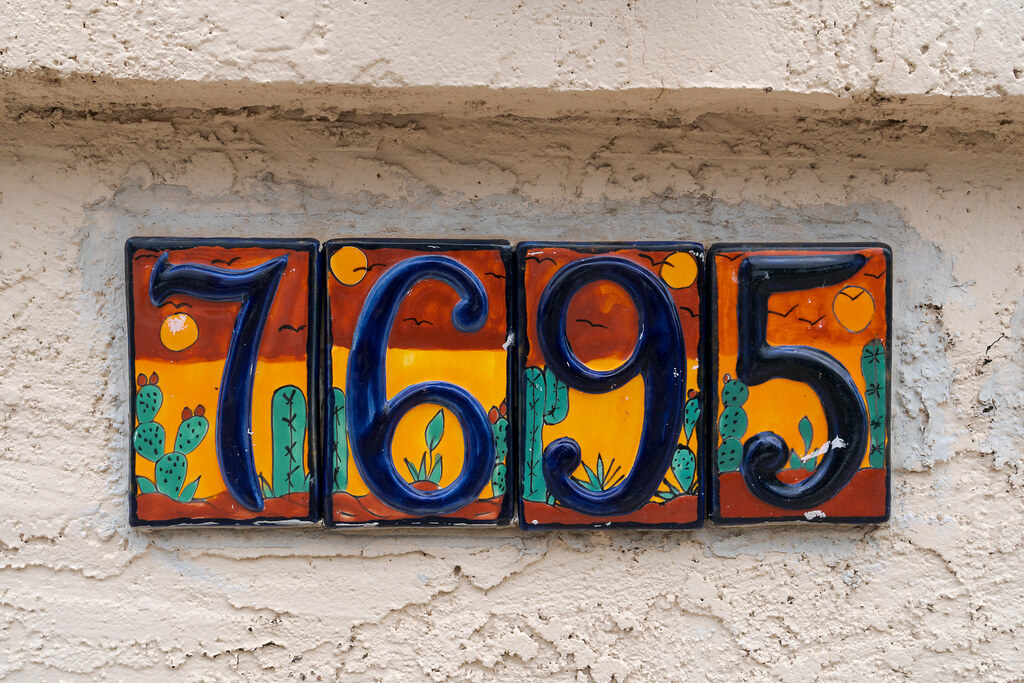 Tiles decorated in a desert motif on a mailbox say '7695'