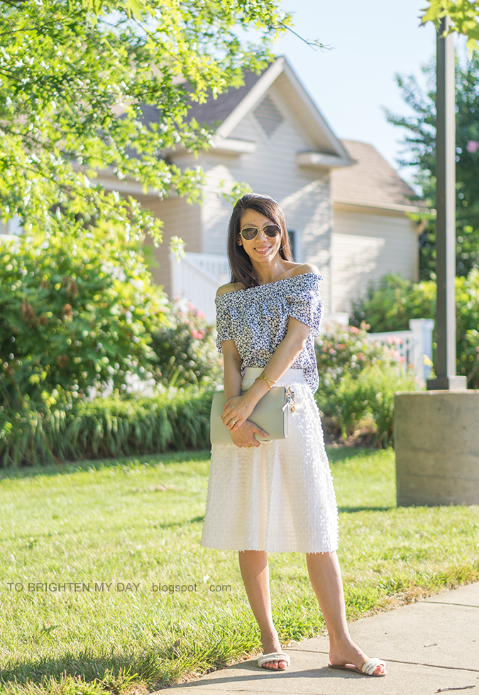 off the shoulder floral top, gold jewelry, blue gray clutch, white clip dot midi skirt, white sandals with fringe